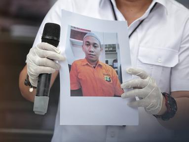 Polisi menunjukkan foto tersangka pengancam pemenggalan terhadap Presiden Joko Widodo atau Jokowi di Mainhall PMJ, Jakarta, Senin (13/5/2019). Di hadapan polisi, tersangka Hermawan Susanto mengaku khilaf dengan perbuatannya tersebut. (Liputan6.com/Faizal Fanani)