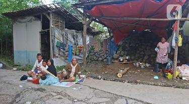 Warga mengungsi di tenda yang didirikannya di jalan Desa Sumber Urip Pebayuran, Senin (22/2/2021). Sudah tiga hari warga bertahan di tenda pengungsian dikarenakan banjir luapan sungai Citarum yang merendam permukiman warga kampung Babakan Banten Pebayuran. (Liputan6.com/Herman Zakharia)