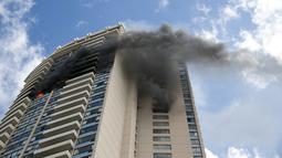 Kepulan asap hitam menyelimuti bagian gedung saat terjadi kebakaran di apartemen Marco Polo, Honolulu (14/7). Menurut petugas setempat, titik api pertama kali muncul di lantai 26 hingga akhirnya menjalar ke beberapa bagian gedung. (AP Photo/Marco Garcia)