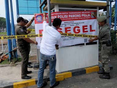 Satuan Polisi Pamong Praja (Satpol PP) Kota Tangerang Selatan menyegel areal parkir liar di kawasan BSD, Rabu (3/10). Penyegelan loket parkir tersebut dilakukan lantaran pihak pengelola parkir tidak memiliki izin. (Merdeka.com/Arie Basuki)