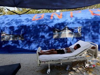 Pasien tertidur di halaman Rumah Sakit Undata, Palu, Sulawesi Tengah, Kamis (4/10). Puluhan pasien korban gempa bumi dan tsunami Palu dirawat dengan kondisi seadanya. (Liputan6.com/Fery Pradolo)