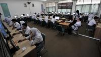 Guru mengawasi yang mengikuti Ujian Nasional Berbasis Komputer (UNBK) di Sekolah Menengah Kejuruan Negeri  (SMKN) 50 Jakarta, Senin (25/3). Sebanyak 69.407 siswa dari 578 SMK di DKI Jakarta mengikuti UNBK yang diselenggarakan pada 25-28 Maret 2019. (merdeka.com/Iqbal S. Nugroho)