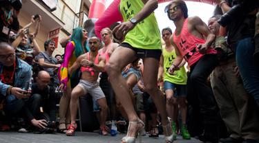 Para peserta mengikuti lomba lari menggunakan sepatu high heels selama peringatan World Pride di distrik Chueca, area populer untuk komunitas gay, di Madrid, Kamis (29/6). World Pride merupakan acara terbesar bagi forum LGBT. (AP Photo/Paul White)