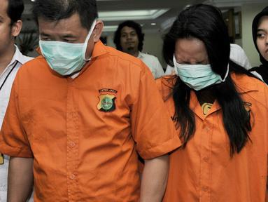 Polisi menggiring dua tersangka L dan G saat rilis tindak pidana penipuan penjualan valas di Mapolda Metro Jaya, Jakarta, Senin (10/2). Dalam kasus ini polisi mengamankan dua tersangka yang merupakan suami istri. (Merdeka.com/Iqbal Nugroho)