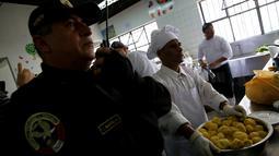 Seorang petugas berdiri di samping narapidana yang tengah membuat masakan dalam kompetisi kuliner 'INPE Mistura 2016' di penjara perempuan Chorrillos di Lima, Peru, Rabu (7/9). Kompetisi masak antar penjara ini diadakan setiap tahun (REUTERS/Mariana Bazo)