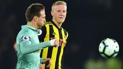 Bek Arsenal, Nacho Monreal berebut bola dengan gelandang Watford, Will Hughes dalam laga lanjutan Premier League 2018-19 pekan ke-34 di Vicarage Road, Senin (15/4). Arsenal sukses mengalahkan tuan rumah Watford dengan skor tipis 1-0. (Ben STANSALL / AFP)