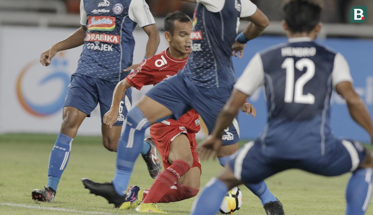 Gelandang Persija Jakarta, Riko Simanjuntak, berusaha melewati beberapa pemain Arema FC pada laga Liga 1 di SUGBK, Jakarta, Sabtu (31/3/2018). Persija menang 3-1 atas Arema FC. (Bola.com/M Iqbal Ichsan)
