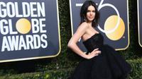 Model cantik, Kendall Jenner menghadiri karpet merah Golden Globe Awards 2018 di California, Minggu (7/1). Dengan model gaun ini, Kendall Jenner memperlihatkan bahu seksi dan kaki jenjangnya di atas karpet merah. (Frazer Harrison/Getty Images/AFP)