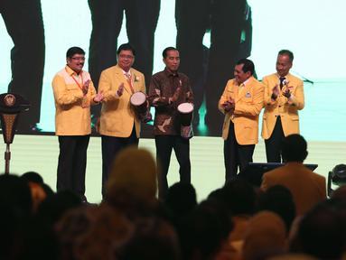 Presiden Joko Widodo (tengah) bersama Ketua Umum Partai Golkar Airlangga Hartarto (kedua kiri) memukul Tifa saat membuka Musyawarah Nasional Luar Biasa (Munaslub) Partai Golkar di Jakarta, Senin (18/12). (Liputan6.com/Angga Yuniar)