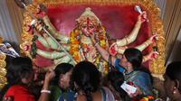 Perempuan Hindu menyuapi makanan untuk dewi Durga pada hari terakhir festival Durga Puja di Hyderabad, India (11/10). Festival Durga Puja merupakan festival tahunan terbesar di Asia Selatan untuk memuja dewi Durga di agama Hindu. (AP Photo/ Mahesh Kumar)