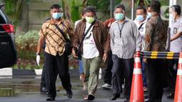 Petugas KPK membawa sejumlah orang yang diamankan dalam operasi tangkap tangan (OTT) Bupati Banggai Laut Wenny Bukamo Dalam OTT di Kabupaten Banggai Laut dan Kabupaten Luwuk, Sulawesi Tengah pada Kamis (3/12) ke dalam gedung KPK, Jakarta, Jumat (4/12/2020). (Liputan6.com/Helmi Fithriansyah)