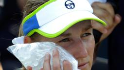 Petenis Rusia, Ekaterina Makarova menaruh es di wajahnya karena kepanasan saat istirahat bertanding melawan Julia Goerges asal Jerman di putaran kedua AS Terbuka, New York, Rabu (29/8). (AP Photo/Seth Wenig)