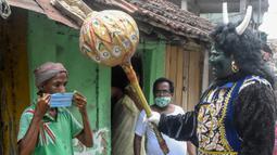Seorang pria berkostum dewa kematian Yamaraj saat mengimbau warga yang tidak memakai masker di tengah lockdown di Kolkata, India (24/4/2020). (AFP/Dibyangshu Sarkar)