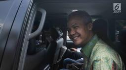 Gubernur Jawa Tengah Ganjar Pranowo tersenyum saat berada di dalam mobil usai diperiksa di gedung KPK, Jakarta, Selasa (4/7). Ganjar Pranowo diperiksa sebagai saksi untuk kasus dugaan korupsi proyek pengadaan e-KTP. (Liputan6.com/Helmi Afandi)