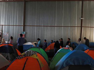 Imigran mengantre makanan di dalam tempat penampungan di Tijuana, Meksiko 6 April 2019. Rombongan migran Amerika Tengah mencapai kota perbatasan antara Meksiko dan AS tersebut  untuk mencari suaka akibat kekerasan, pembunuhan dan kemiskinan yang mengancam