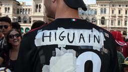 Seorang tifosi AC Milan mengenakan jersey bernama Higuain sebelum kedatangan pemain Argentina tersebut di alun-alun pusat Milan Piazza Duomo (3/8). Higuain akan membela I Rossoneri hingga 30 Juni 2019 dengan status pinjaman. (AFP Photo/Stringer)