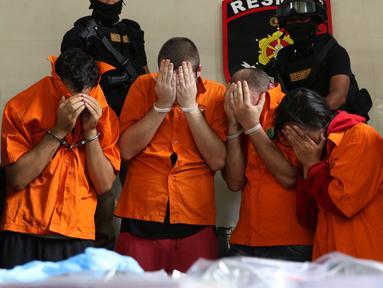 Lima tersangka pembobol uang dari mesin ATM dengan teknik skimming diperlihatkan petugas Resmob Polda Metro Jaya saat rilis di Jakarta, Sabtu (17/3). Sindikat ini membobol 64 bank pada sejumlah negara. (Liputan6.com/Helmi Fithriansyah)