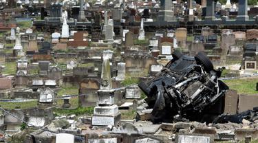 Kondisi mobil SUV Mercedes usai menabrak nisan di sebuah pemakaman di pinggiran selatan South Coogee, Australia (6/2). Pengemudi 49 tahun yang membawa mobil tersebut dibawa ke rumah sakit setelah menabrakkan mobilnya ke pemakaman. (AFP Photo/William West)