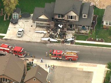 Personel darurat berada di lokasi sebuah pesawat kecil yang menabrak rumah di Payson, Utah, AS, Senin(13/8). Pesawat bermesin ganda Cessna 525 itu sengaja ditabrakkan seorang pria, Duane Youd ke rumahnya sendiri. (John Wilson/KSL-TV/Deseret News via AP)