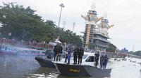 Kepala Dinas Pemuda dan Olahraga Kalimantan Selatan, Drs. Zakli Asswan, MM membawa obor Asian Games melintasi sungai Barito, Senin (30/7/2018). (Bola.com/Reza Bachtiar)