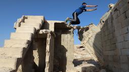 Seorang pemuda Suriah melakukan parkour di atas reruntuhan bangunan yang hancur akibat serangan pasukan rezim di kota Binnish di provinsi barat laut Idlib pada 17 Juni 2020. Parkour merupakan olahraga ketangkasan yang terdiri dari lari, melompat, salto dan berayun. (Abdulaziz KETAZ / AFP)