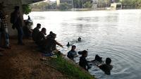 Polisi mencari benda yang diyakini mampu mengungkap misteri kematian mahasiswa Universitas Indonesia (UI) Akseyna Ahad Dori di danau UI. (Liputan6.com/Atem Allatif)