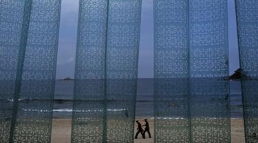 Dua pria terlihat dari tirai plastik sebuah restoran berjalan di pantai Sijung Ho di Korea Utara (14/7/2019). Pantai Sijung Ho merupakan tujuan wisata populer bagi penduduk lokal dan asing. (AP Photo/Vincent Yu)