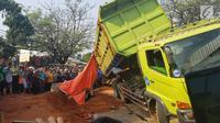 Warga berkerumun menyaksikan proses evakuasi bangkai mobil kecelakaan maut yang hancur tertindih badan truk muatan tanah di Karawaci, Tangerang, Kamis (1/8/2019). Sopir truk yang menimpa mobil dan menewaskan 4 orang itu kabur setelah kecelakaan maut terjadi. (Liputan6.com/Pramita Tristiawati)