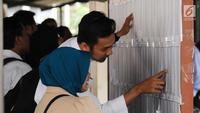Peserta tes seleksi CPNS Kemenkumham mengecek no pendaftaran di gedung BKN, Jakarta, Senin (11/9). Pada 2017, tercatat 1.116.138 pelamar CPNS mendaftar di lingkungan Kemenkumham. (Liputan6.com/Helmi Fithriansyah)