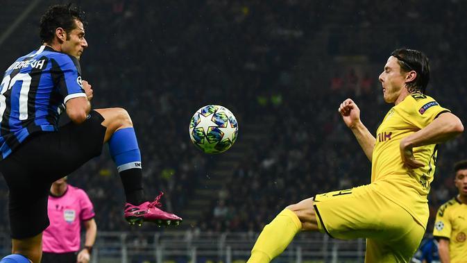 Gelandang Inter Milan, Antonio Candreva berebut bola dengan bek Borrusia Dortmund, Nico Schulz  pada pertandingan lanjutan Grup F Liga Champions di stadion San Siro, Italia (23/10/2019). Inter Milan menang 2-0 atas Dortmund. (AFP Photo/Miguel Medina)
