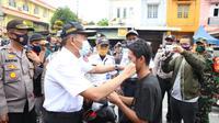 Menko PMK juga membagi-bagikan masker kepada masyarakat sekitar lingkungan kampus UMSU.