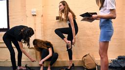 Model memakai sepatu saat menunggu casting untuk Melbourne Fashion Week, Australia (24/7/2019). Lebih dari 400 model tampil di Melbourne Meat Market yang ikonik menjadi salah satu dari 120-150 model yang dipilih untuk mode tersebut. (AFP Photo/William West)
