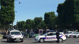Kendaraan polisi Prancis menutup akses jalan Champs Elysees di Paris, Prancis, Senin (19/6). Sebuah mobil mengeluarkan api usai sengaja menabrak kendaraan polisi di lokasi wisata terkenal tersebut yang menewaskan pengemudinya (AP Photo/Matthieu Alexandre)