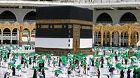 Jemaah mengelilingi Kabah pada awal musim haji di Masjidil Haram, Mekkah, Arab Saudi, Sabtu (17/7/2021). Jumlah jemaah yang akan melaksanakan ibadah haji tahun ini sebanyak 60 ribu. (AFP)