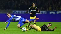 Pemain Borussia Dortmund, Julian Weigl dan pemain Hertha Berlin Ondrej Duda terjatuh saat berebut bola pada lanjutan Bundesliga di Olympiastadion Berlin, Sabtu (20/1). Hasil imbang 1-1 mengakhiri duel antara Hertha Berlin vs Dortmund. (Tobias SCHWARZ/AFP)