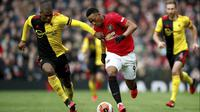 Pemain Manchester United Anthony Martial (kanan) menggiring bola melewati pemain Watford Christian Kabasele pada pertandingan Liga Inggris di Old Trafford, Manchester, Inggris, Minggu (23/2/2020). Manchester United menang 3-0. (Martin Rickett/PA via AP)