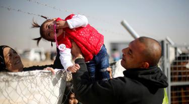Seorang pria menyeberangkan anak perempuan melewati kawat berduri di kamp pengungsian Khazer, Irak (28/11). Mereka pergi meninggalkan daerah yang sebelumnya dikuasai kelompok militan ISIS untuk mengungsi ke tempat yang lebih aman. (Reuters/Mohammed Salem)