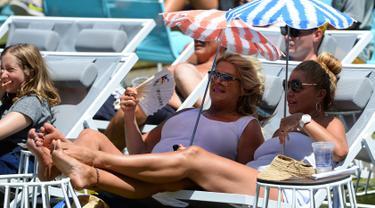 Dua penonton wanita duduk sambil membawa payung kecil menyaksikan serunya pertandingan tenis selama putaran pertama Australian Open 2017 di Melbourne, Australia (16/1). (AFP Photo/Greg Wood)