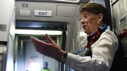 Pramugari Bette Nash menyapa penumpang sebelum melakukan penerbangan ke Boston di Bandara Ronald Reagan Washington di Arlington, Virginia (19/21). Bette Nash adalah pramugari tertua di maskapai American Airlines. (AFP Photo/Eric Baradat)