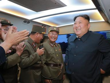 Pemimpin Korut Kim Jong-Un tersenyum setelah mengamati tembakan dua rudal taktis terbaru di lokasi bagian barat yang dirahasiakan (7/8/2019). Peluncuran rudal terbaru negaranya, adalah peringatan keras bagi Washington dan Seoul atas rencana latihan militer kedua negara. (KCNA VIA KNS/AFP)