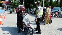 Polisi lalu lintas memberhentikan pengemudi sepeda motor dalam razia pajak kendaraan di Pekanbaru. (Liputan6.com/M Syukur)