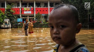 Anak-anak melintasi banjir yang melanda kawasan bantaran kali Cisadane, Tangerang, Jumat (26/4). Banjir kiriman setinggi 2 meter sempat melanda kawasan akibat curah hujan yang tinggi di bogor membuat derasnya air mengalir jauh sampai ke tempat ini. (Liputan6.com/Johan Tallo)
