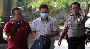 Kepala Kantor Imigrasi Kelas I Mataram Kurniadie (tengah) tiba di Gedung KPK, Jakarta, Selasa (28/5/2019). Kurniadie menutupi mukanya dengan masker saat tiba di Gedung KPK. (Liputan6.com/HO/Joni)