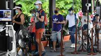 Pengunjung menunjukkan kode masuk mereka saat melalui area pemeriksaan suhu pada hari pertama pembukaan Kebun Binatang Singapura, Senin (6/7/2020). Kebun binatang yang hampir tiga bulan ditutup akibat pandemi virus corona ini dibuka kembali dengan penerapan protokol kesehatan. (Roslan RAHMAN/AFP)