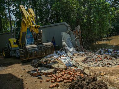 Petugas UPK Badan Air DLH Provinsi DKI Jakarta dibantu alat berat memperbaiki tembok Kali Krukut yang jebol di Jalan Taman Kemang, Jakarta, Selasa (23/2/2021). Jebolnya tembok tersebut mengakibatkan kawasan kemang dan sekitarnya terendam banjir pada 20 Februari 2021. (Liputan6.com/Faizal Fanani)