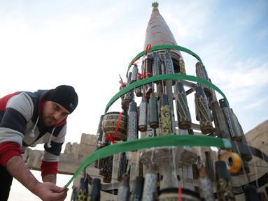 Pria Suriah bernama Akram Abu al-Foz membuat sebuah pohon natal dari sisa-sisa amunisi di Douma, Suriah, Jumat (23/12). Akram membuat karya ini untuk menyemarakkan Hari Natal di tengah konflik yang terjadi di Suriah.(REUTERS/Bassam Khabieh)
