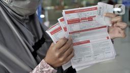 Warrga menunjukkan formulir pembatalan perjalanan kereta api di Stasiun Pasar Senen, Minggu (29/3/2020). PT KAI Daop 1 Jakarta membatalkan sejumlah perjalanan keberangkatan kereta jarak jauh hingga 1 Mei 2020 sebagai pencegahan penyebaran virus Corona. (merdeka.com/Iqbal Nugroho)
