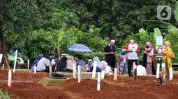 Peziarah berdoa di sisi makam jenazah yang diduga terinfeksi virus COVID-19 di TPU Pondok Ranggon, Jakarta, Minggu (24/5/2020). Momen Hari Raya Idul Fitri 1441 H dimanfaatkan sejumlah keluarga dan kerabat korban yang diduga terinfeksi COVID-19 untuk berziarah. (Liputan6.com/Helmi Fithriansyah)