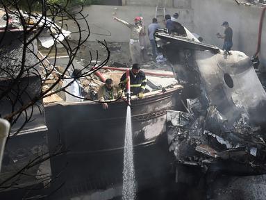 Petugas pemadam kebakaran menyemprotkan air pada puing pesawat Pakistan International Airlines yang jatuh di Karachi, Pakistan, Jumat (22/5/2020). Menurut perwakilan dari Kementerian Kesehatan Sindh, 97 orang dilaporkan meninggal dan dua orang selamat dalam kecelakaan tersebut. (Rizwan TABASSUM/AFP)