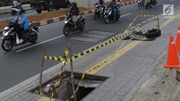 Pengendara melintas di dekat penutup trotoar yang rusak di kawasan Jalan RS Fatmawati, Jakarta, Selasa (14/7/2019). Dua buah penutup trotoar di Jalan RS Fatmawati rusak parah, kondisi ini mengganggu kenyamanan dan membahayakan pejalan kaki, terutama pada malam hari. (Liputan6.com/Helmi Fithriansyah)